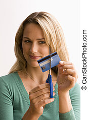 Woman Cutting Up Credit Card - A young woman is cutting...
