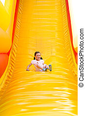 Girl Sliding - Happy little girl having lots of fun on a...