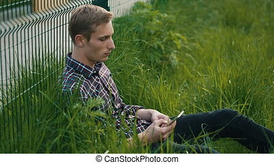 Young man sitting on the grass with cellphone - Young man...