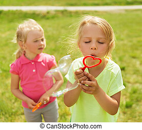 group of kids blowing soap bubbles outdoors