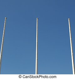 Flagpole flagstaff mast over a blue sky background