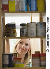 Woman Looking in Kitchen Cupboards - A young woman is...