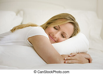 Woman Sleeping in Bed - A young woman is lying on her bed...