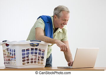 Man Using Laptop While Doing the Laundry - A man is working...