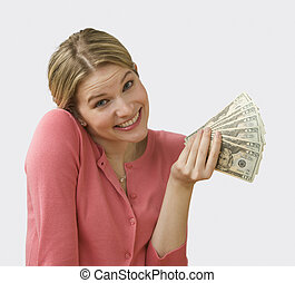 Woman Holding Cash - Beautiful young woman fans out cash and...