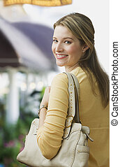 Woman Smiling over Shoulder - A young woman is smiling over...