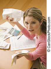 Woman Paying Bills - A young woman looks upset while sorting...