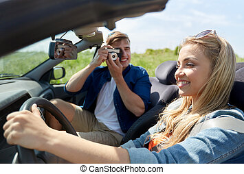 man photographing woman driving car by film camera -...