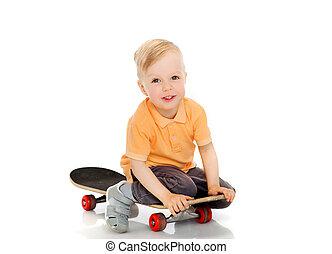 happy little boy sitting on skateboard - childhood, sport,...