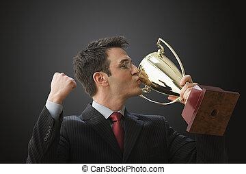 homem negócios, beijando, troféu