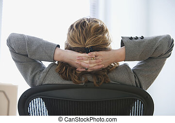 Businesswoman Relaxing in Office Chair - A businesswoman is...
