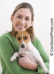 Attractive Young Woman Holding A Dog And Smiling - A...