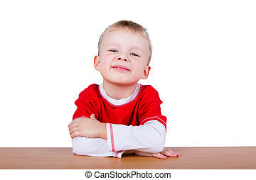 Small boy in red T-shirt, sitting at the table. Isolated on...
