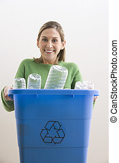 Attractive Young Woman Holding a Blue Recycle Bin - An...