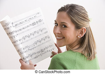 Attractive Young Woman Holding Sheet Music And Smiling - An...