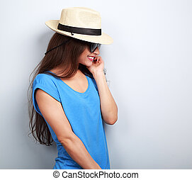 Beautiful young woman profile in straw hat and fashion sunglasses in blue top laughing