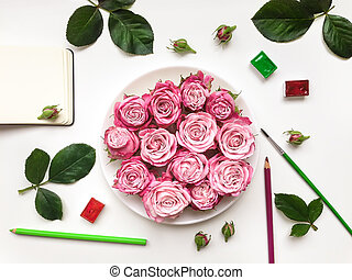 Colorful composition with roses, sketchbook and accessories....