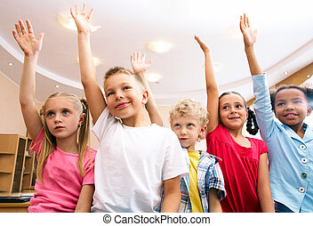 Answering - Image of pupils raising arms during the lesson