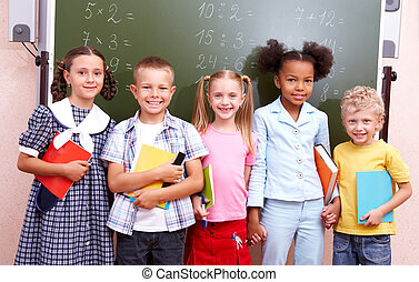 In the classroom - Image of curious schoolchildren standing...