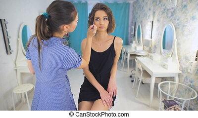 Pleasant woman stylist, working with mascara.