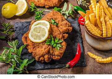 Schnitzel with fries, salad and herbs, hot chilli tomato...