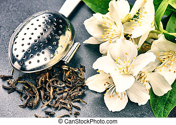 Tea infuser spoon with dry green tea leaves and jasmine flowers