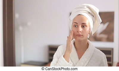 Beautiful woman applying skincare lotion to face caring for...