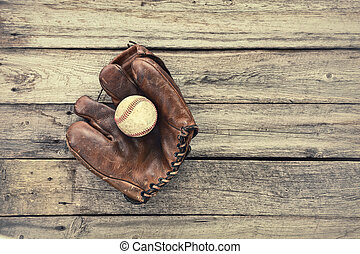 Old leather baseball mitt and ball on grunge wood background...