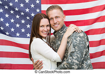Male Soldier With His Wife In Front Of American Flag -...