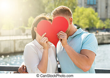Couple Hiding Behind Heart Shape