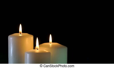 footage burning candles isolated on a black background 4K...