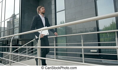 Side view of young businessman walking in passage of office with laptop
