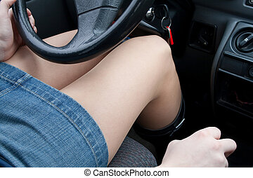 Woman driving a car - Young adult woman woman in mini skirt...