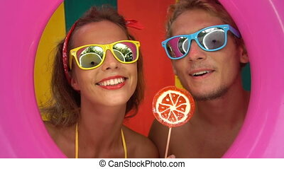 Funny couple licking orange lollipop - Funny young couple...