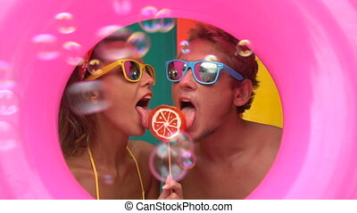 Couple with bubbles and lollipop - Funny young couple eating...