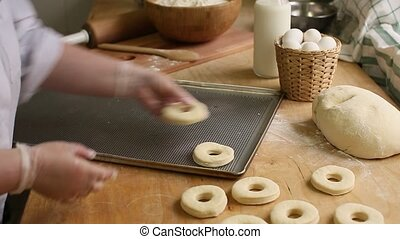 Chef cooks on protoven blank donuts, bagel - Female chef...