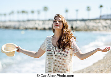 Woman with open arms deep breathing in the beach. -...