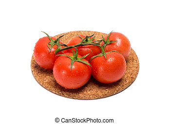 Sprig of red tomato with water drops on a cork base on a...