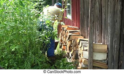man guy stack chopped wood near village house wall. 4K - man...