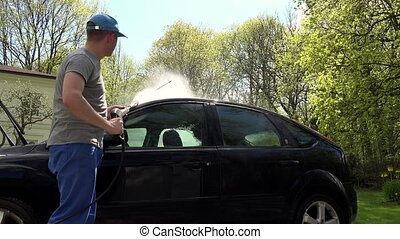 Man, hosing his car at do it yourself car wash, using high pressure water spray