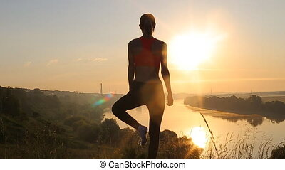 Young woman silhouette practicing yoga at sunrise.