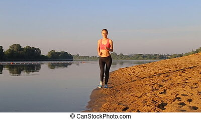 woman with a slender figure is engaged in gymnastics at rives at sunrise.