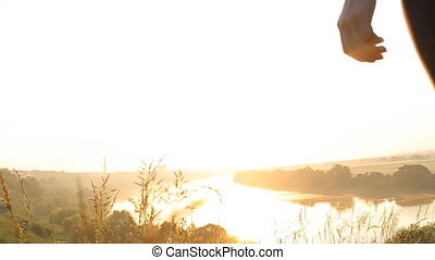 SLOW MOTION CLOSE UP: Young woman raising her hands on top of the mountain