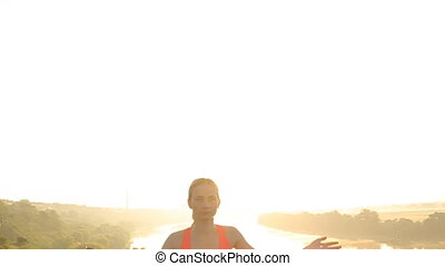 Young woman silhouette practicing yoga at sunset. Slim woman...