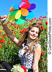 girl with windmill in poppy field