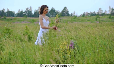 Beautiful young girl with flowers in summer field. Slim...