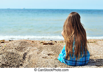 solitude near the sea - young longhaired woman sitting alone...
