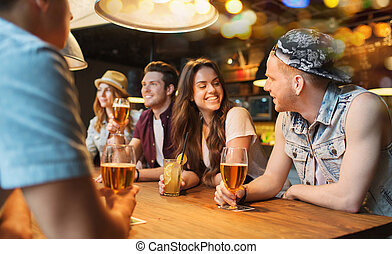 happy friends with drinks talking at bar or pub - people,...