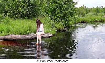 Girl on lake log relaxing - Girl on wild lake relaxing on...