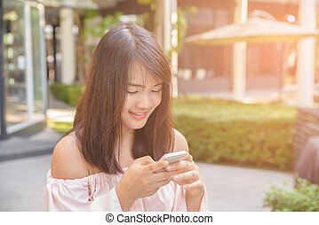 Charming young woman in white shirt reads or texts message...